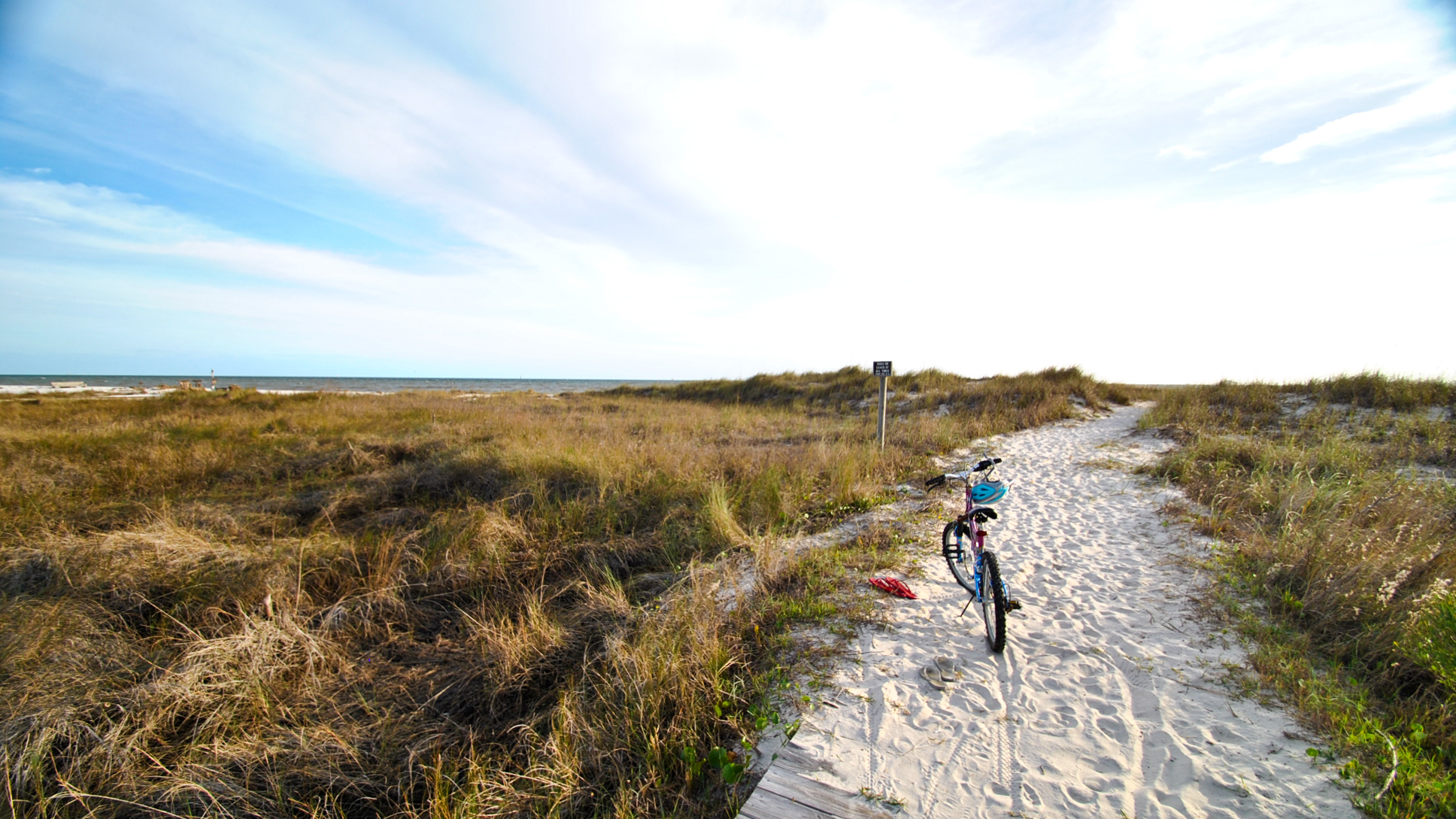 Bicycling on a bike trail on the beach, behind De Soto Landings, on Dauphin Island Alabama. There are many vacation home rentals with pools in De Soto Landings