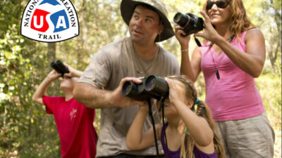 Family birdwatching with binoculars Dauphin Island's Audubon Bird Sanctuary